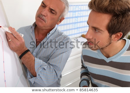 Teacher and pupil looking at graph on whiteboard Stock photo © photography33
