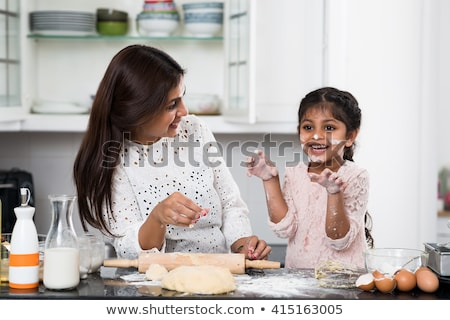 portrait of cheerful mother and daughter in flour in kitchen Stock photo © LightFieldStudios