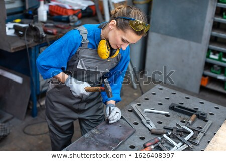 Sideview of worker woman marking piece of metal Stock photo © Kzenon