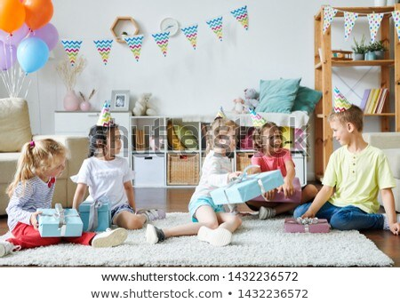 Group of happy adorable kids in birthday caps sitting on rug Stock photo © pressmaster