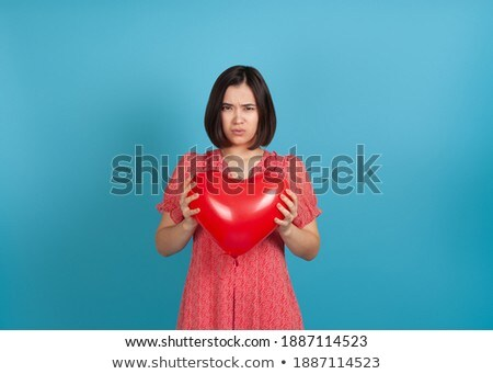 offended young girl holding heart shaped balloon stock photo © deandrobot