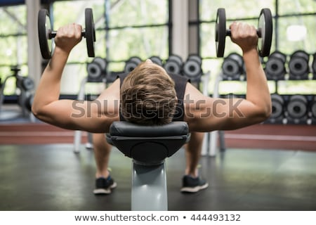 Stock photo: Man lifting dumbbell weights while lying down