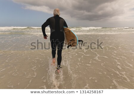 Vista posteriore attivo senior uomo esecuzione tavola da surf Foto d'archivio © wavebreak_media