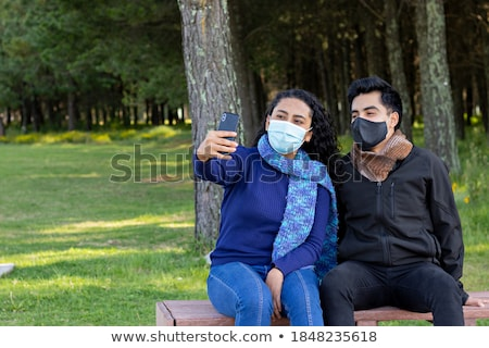 Photo of adult man walks at street, wears protective mask and rubber gloves as protection against in Stock photo © vkstudio
