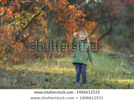 Funny kid girl pretending to be posing in autumn forest, wearing a green coat Stock photo © ElenaBatkova