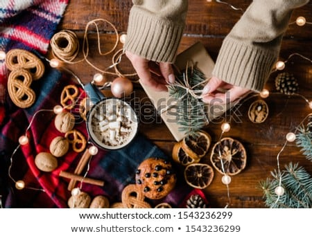 View of hands of young woman by table making knot on top of giftbox Stock photo © pressmaster