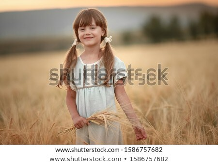 A girl with spikelets in her hands and braids in her hair in a wheat field Stock photo © ElenaBatkova