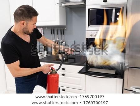 Adam yangın söndürücü dışarı yangın fırın ev Stok fotoğraf © AndreyPopov