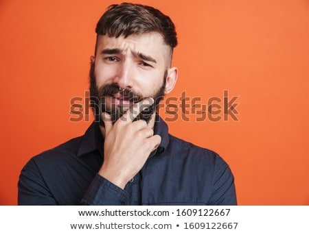 Image of serious man with nose jewelry thinking and touching his Stock photo © deandrobot