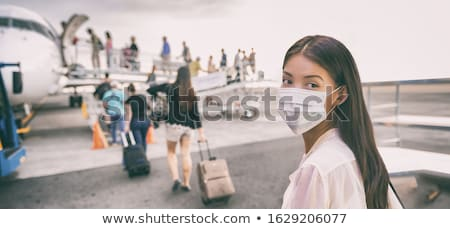 Airport Asian woman tourist boarding plane taking a flight in China wearing face mask. Coronavirus f Stock photo © Maridav