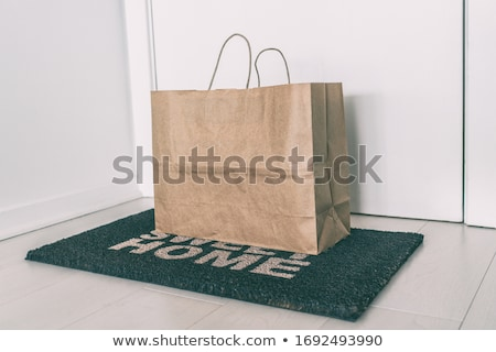 Home delivery of food grocery bag left at door entrance mat for Corona virus prevention safety. Prec Stock photo © Maridav