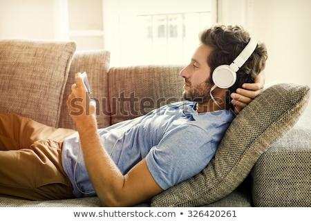 Young man listening music with headphones and resting on couch. Stock photo © lichtmeister