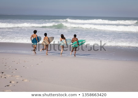 Rear view of shirtless young male surfer with surfboard running on beach in the sunshine Stock photo © wavebreak_media