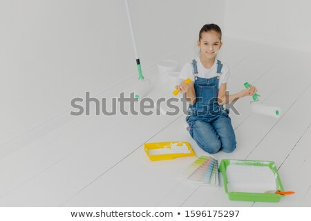 Top view of small European girl in denim overalls stands on knees, uses paint rollers, helps parents Stock photo © vkstudio