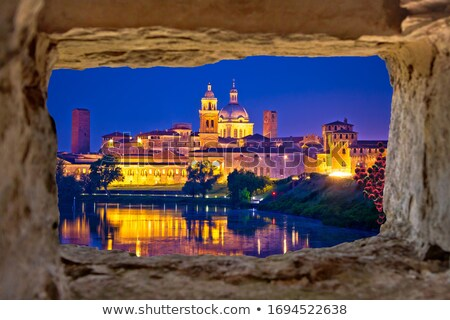 City of Mantova skyline evening view through stone window Stock photo © xbrchx