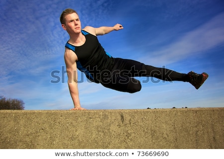 young man jumping over wall on obstacle course stock photo © ammentorp