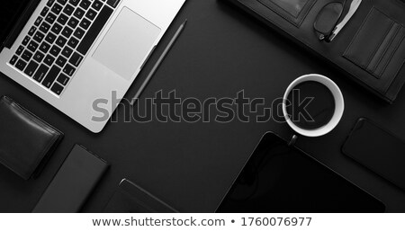 Business desktop concept. Mix of office supplies and gadgets on a black table background Stock photo © dash