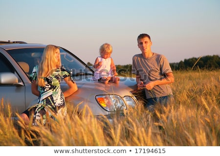 Parents and child sitting on car cowl on wheaten field Stock photo © Paha_L