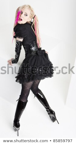 standing young woman wearing extravagant boots Stock photo © phbcz