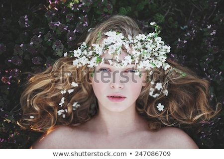 Beautiful girl with flower in hair on the grass stock photo © pekour