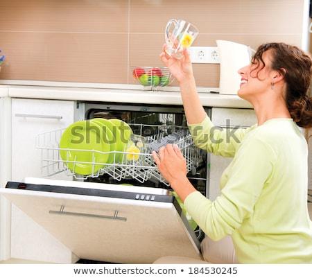 Smiling young woman using a dishwasher Stock photo © wavebreak_media