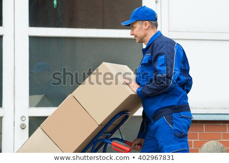 Stock photo: Mature courier man carrying stack of cardboard boxes
