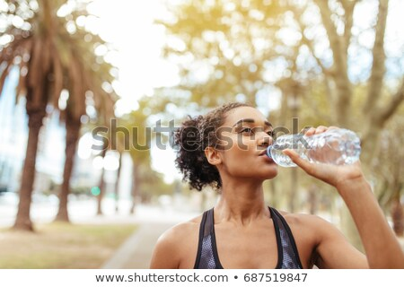 young woman drinking water during her workout stock photo © studio1901