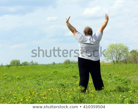 overweight woman with hands up on meadow Stock photo © Mikko