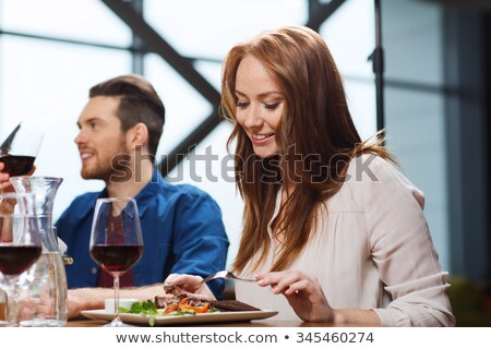 smiling young woman eating main course Stock photo © dolgachov