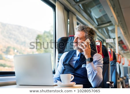 Stock fotó: Businessman Commuting To Work On Train And Using Laptop
