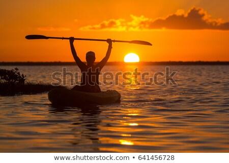 kayakers silhouette on ocean during orange sunset stock photo © jameswheeler