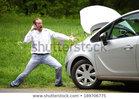 Driver furious with mobile phone a broken car by the road Stock photo © vladacanon