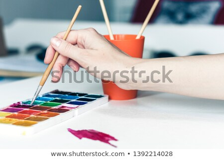 set of watercolor paints used by woman artist on table stock photo © deandrobot