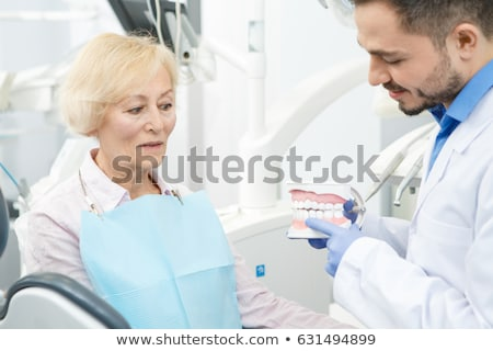 Foto stock: Male Dentist Showing His Female Patient A Dental Implant