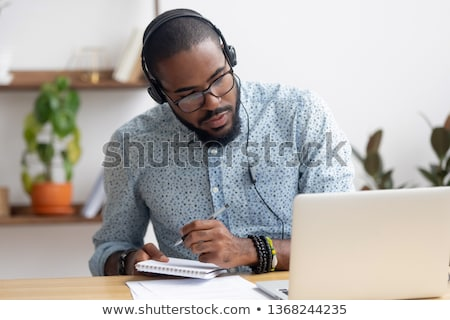 concentrated young businessman sitting and reading notes in notebook stock photo © deandrobot