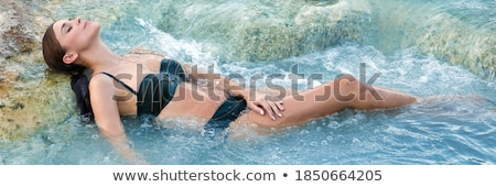 Brunette beauty taking bath in a waterfall Stock photo © konradbak