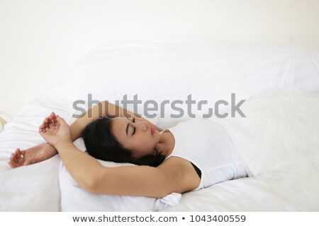 pretty indian brunette real woman in bed smiling white sheets stock photo © iordani