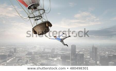 business man hanging on balloon stock photo © rastudio