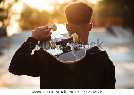 back view of a male teenager guy holding skateboard stock photo © deandrobot