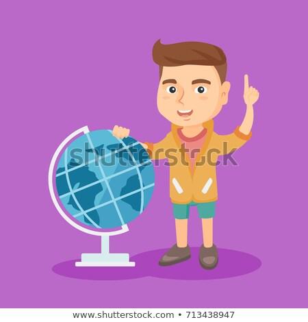 boy standing near globe and pointing finger up stock photo © rastudio