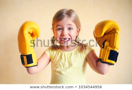 Stock foto: Little Girl With Yellow Boxing Gloves Over Yellow Wall Backgroun