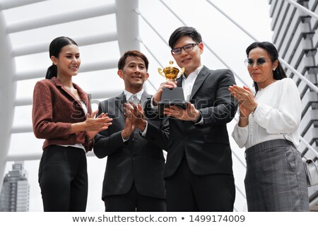 Stock photo: Asian businessman hold golden award cup