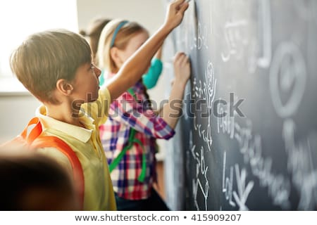 Girl writing a sum on a blackboard Stock photo © IS2
