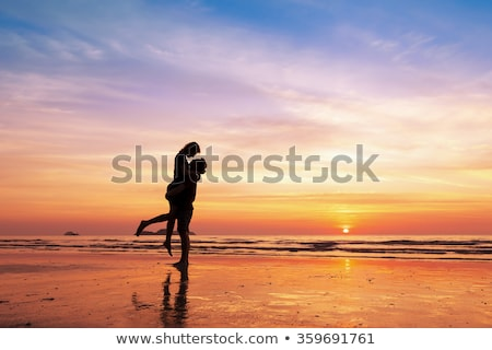 Stock photo: Couple kissing in sunrise at the beach.