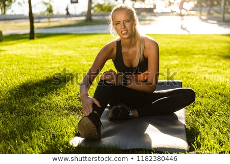 Sad young blonde sports woman with painful feelings in park outdoors touching her leg. Stock photo © deandrobot
