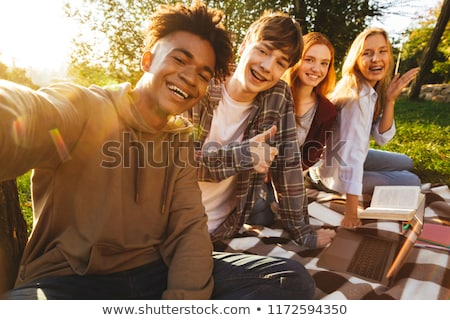 group of cheerful multhiethnic students doing homework stock photo © deandrobot