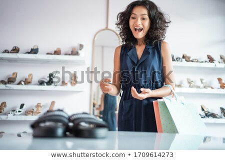 excited young woman choosing shoes at store stock photo © dolgachov