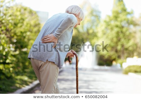 Foto stock: Elderly Woman Outdoors With Back Pain