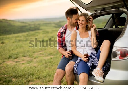 loving couple sitting in the car trank stock photo © boggy