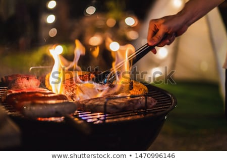 happy friends grilling food and enjoying barbecue party outdoors stock photo © boggy